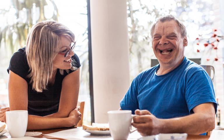 Person with disability smiling next to carer