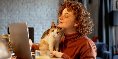 Young woman with pet cat using laptop